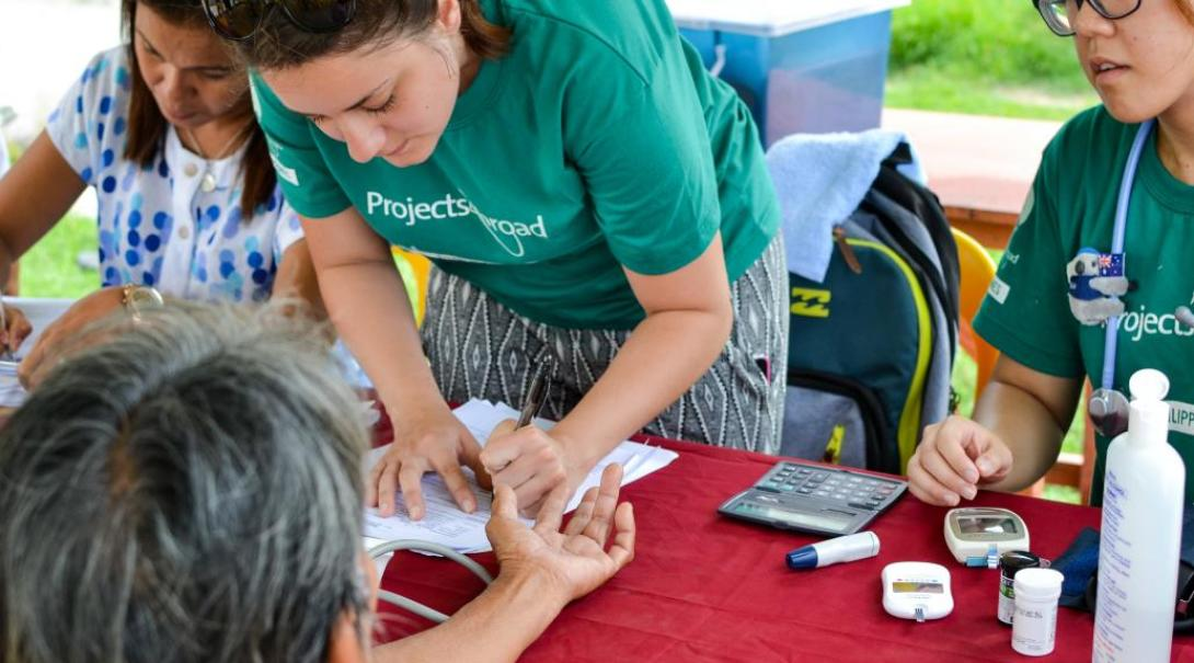 A high school student measures blood sugar during a community healthcare outreach in the Philippines